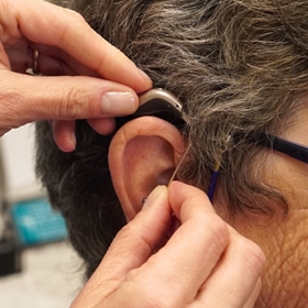 Fitting a hearing aid device on client at Frontenac Hearing Clinic in Kingston Ontario.